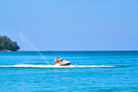 Ð¡ouple, man and woman enjoy riding ski jet in blue ocean. Island on backgraund