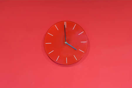 Red round glass clocks hang on a red wall. Shows the current time 4:00 pm