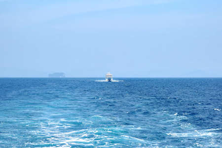 The white ship pursues another ship at sea. Clear sunny day, blue sky Reklamní fotografie