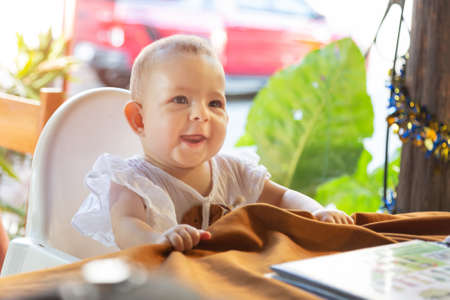 Infant girl is sitting on a baby high chair in a street cafe by the table. Children in white dress dabbles and pulls the tablecloth 免版税图像