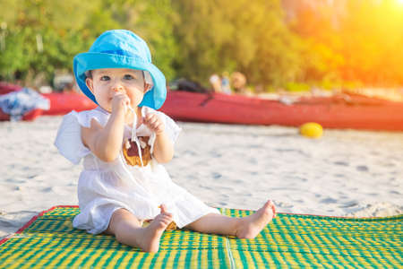 Teething in 8 mounth. Baby girl sitting on the beach and chews a teether. In blue hat and white dress on bamboo mat