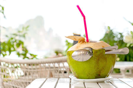 Romantic for two . Fresh coconut juice with straw and two spoons on white wood table against blurred beach and mountain