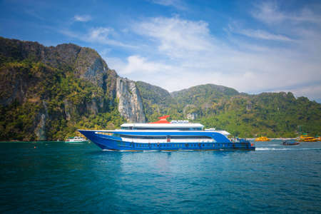 Blue and white passenger ferry ship sailing to destination point. Port with another ships and mountain on background.
