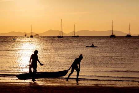 People on the beach play sports in the light of a golden sunset. Kayakers float in the water, two girls carry out to the land of the boat. Against the background of the yacht and the mountains, the reflection of the sun on the water, the path. 스톡 콘텐츠