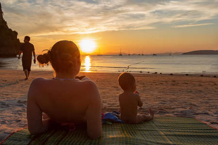Mother with her daughter. Little baby girl of 9 months. Couple sitting back on a tropical beach, watching and enjoy the sunset. Beautiful blue sky, a bit cloudy, golden sunset light. Man leaves
