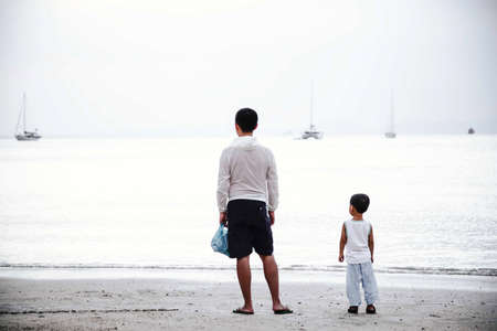 Father in white hoodie and son in tshirt are looking at the sea. Stand back, facing the water. Sandy beach on the background of the yacht. White tones