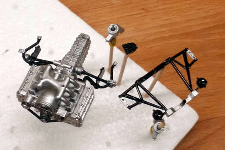 Dry painted plastic parts of cars. Engine, Gearbox, suspension elements, timing belt. Large-scale assembly of models.  Hold on to the toothpicks stuck in the foam. 스톡 콘텐츠
