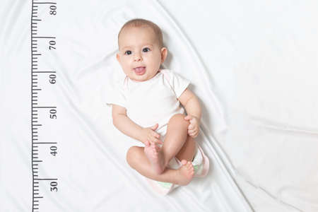 A five month baby in white clothes lying on a bed on which a measuring ruler for growth is drawn. shows the tongue from her mouth and teased Stok Fotoğraf