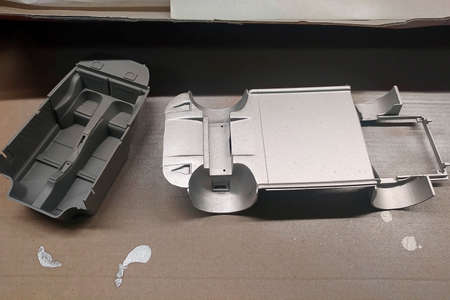 Unprimed and primed parts of a scale model car for assembly. Body and car interior. Modeling. Painting a toy car.