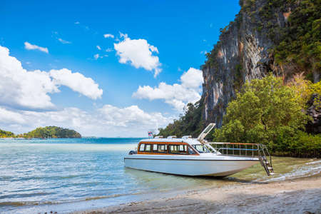 Waiting for passenger. white premium speedboat on the shore of a tropical island. Moored on a sandy beach, Tropics and rocks in the background.