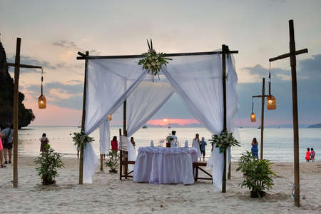 Tourists enjoy the sunset view on the beach. On the sand set table decorated for a romantic dinner. Against the background of the cliff and the sea.