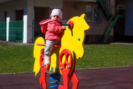 A little girl dressed in a pink jacket is sitting on a yellow toy horse. Baby plays on the playground, sits on the rocking chair. 免版税图像