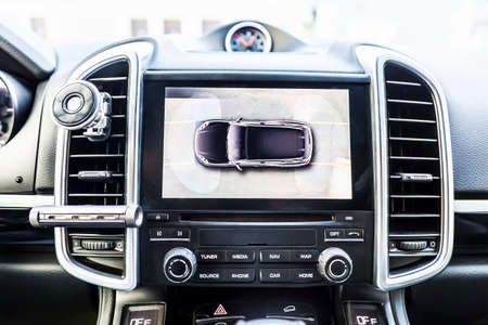 Top view, Display in interior of luxury car shows working of four cameras in surround view assist system. 360 degrees Image display on the head unit. Multimedia in the car.