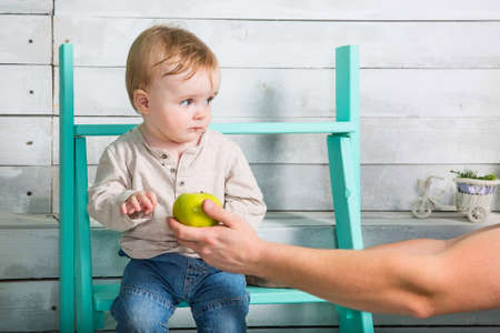 A little boy does not want to take an apple from a stranger. He looks incredulous and sits on the steps indoor. White wooden background