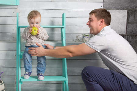 Happy father holds baby boy who eat big green apple. He both are in jeans and white hoodie.  Dad with son sits on the steps indoor. White wooden background
