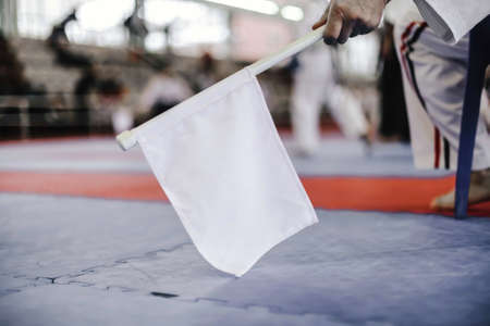 Hand of man who holds a white flag on the background of the stands