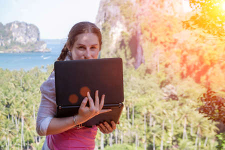 Freelancer girl hiding behind a laptop screen. She stands on the edge of a rock with its back to the sea and tropical forest landscape.