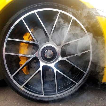 Yellow car with light alloy wheels with carbon ceramic brakes and smoke from it. Close up, square image