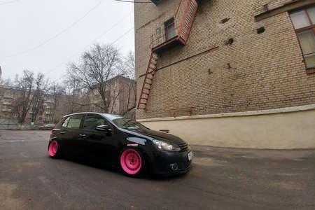Moscow, Russia - May 08, 2019: A black tuned and understated Volkswagen Golf 6 with bright pink handmade custom wheels stands on the street. Low car with air suspension installed Wide angle side view 新聞圖片