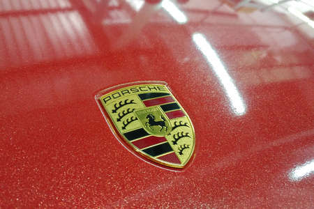 Moscow, Russia - April 14, 2019: Porsche Macan wrapped in bright red metallic color vinyl film. Logo on the hood closeup