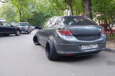 Russia, Moscow - May 04, 2019: Gray metallic Opel Astra modified to Stance style. Car with big custom steel wheels parked on the street. Back side view