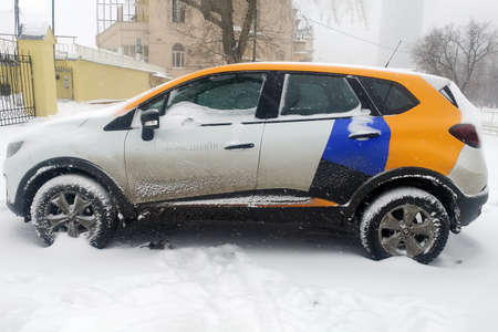 Moscow, Russia - May 08, 2019: Crossover of one of the companies that provide car sharing services. Car of Yandex Drive carshering covered with snow and stands in a snowdrift. Left  side Renault Kaptur Editorial
