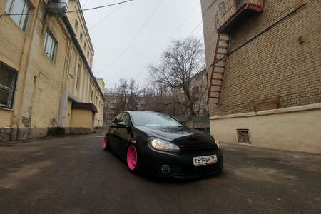 Moscow, Russia - May 08, 2019: A black tuned and understated Volkswagen Golf 6 with bright pink handmade custom wheels stands on the street. Low car with air suspension installed. Wide angle front view