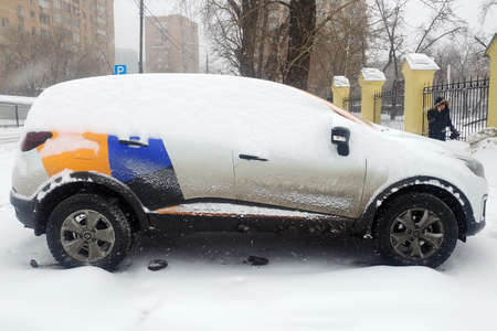 Moscow, Russia - May 08, 2019: Crossover of one of the companies that provide car sharing services. Car of Yandex Drive carshering covered with snow and stands in a snowdrift. Right side Renault Kaptur