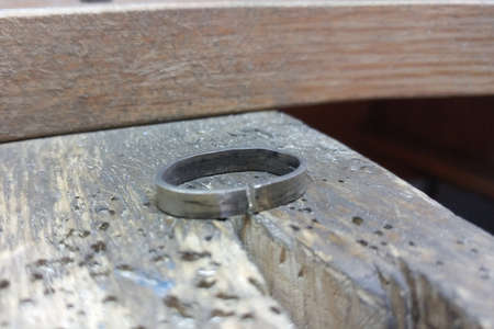 White gold ring blank lies on a wooden work surface. The process of making jewelry. Imagens
