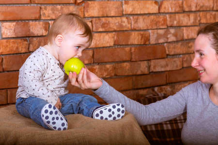 Young mother gives his son an green apple to eat. On a red bricks wall  background. One year baby in jeans sitting