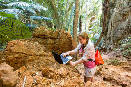 A young woman works with a laptop in the mountains and tropical thickets. Remote work in travel.  Looks at the computer. Freelancer at work.