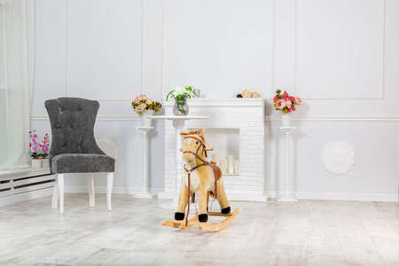 Wooden Rocking Horse. The toy stands on the background of a decorative fireplace and light wall, gray chair near it