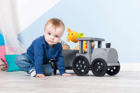 Boy blond in a blue sweater sits on a wooden floor. One year old baby playing with wooden toys.  train made of wood, with girafe inside, blue wall at background
