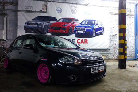Moscow, Russia - May 08, 2019: A black tuned and understated Volkswagen Golf 6 with bright pink handmade custom wheels stands in garage, Low car with air suspension installed