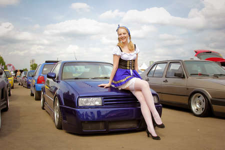 Moscow. Russia - May 20, 2019: A young girl in a national German costume is standing in front of a tuned German car in blue. Stance lowrider stands parked on the street.