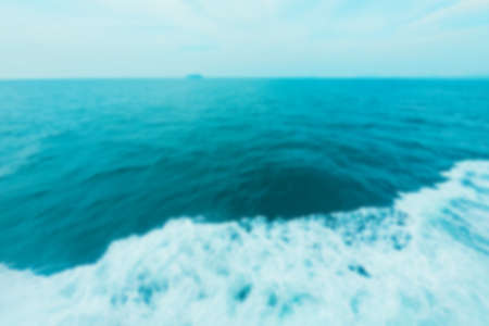 Blurred background. Blue water and horizon line. Waves from a motorboat. Blue tones