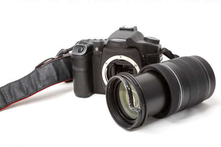 Broken digital SLR camera, dented protective filter on the zoom lens. Will be repaired. Isolated on white background. Side view