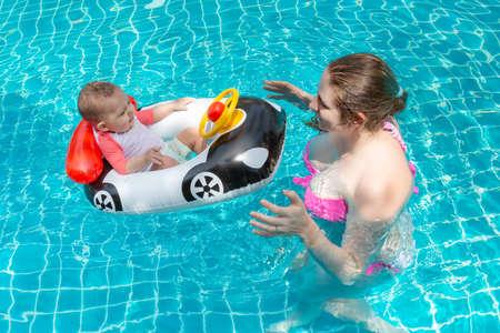 Giovane madre felice in un bikini rosa che si diverte e cattura il bambino in piscina. Un gioioso bambino siede su un gommone a forma di automobile. Tempo libero estivo in mare.