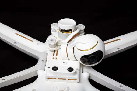 Broken white drone after a fall. Isolated on a black background. Damaged stabilizer camera gimbal. Plugged cable loop Close up. Device to repair