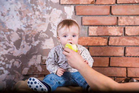 One year old child sits on a barrel against the background of a red brick wall and Ð¿oing to bite off a green apple which is held by his father.