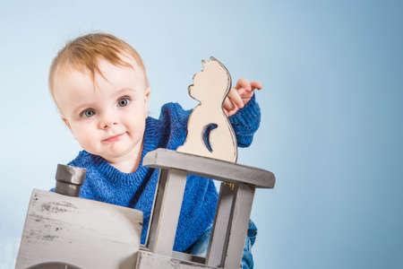 Happy one year old child in a blue sweater plays wooden toys. Blonde baby boy on blue background. Cat and train of wood