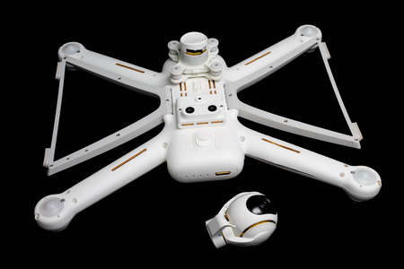 Broken white drone after a fall. Isolate on a black background. Gimbal and camera not repairable