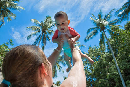Mom raised baby high above the head in the pool. The little girl is very happy and screams for joy. Summer holiday, palm trees and blue sky on the background.