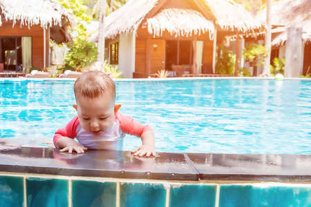 Cute little baby trying to get out of the pool.
