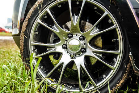 Light alloy wheel of the car is dirty with dirt. The car is on the field.