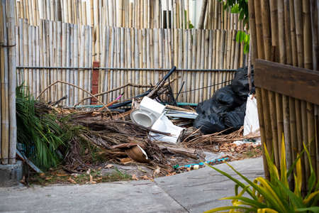 Garbage and other waste on the streets of the tropical island. The toilet is next to the pedestrian walkway. Black bags