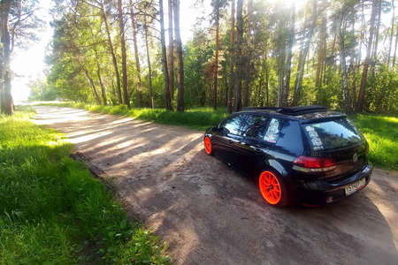 Russia, Moscow - June 01, 2019: Black Volkswagen Golf Mk6 tuned with ragtop and orange wheels. Stance tuning on air suspension in green forest. Back