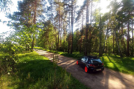 Russia, Moscow - June 01, 2019: Black Volkswagen Golf Mk6 tuned with ragtop soft roof and orange wheels. Stance tuning on air suspension in green forest.
