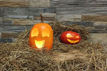 Two halloween jack o lanterns yellow and red on brick wall background