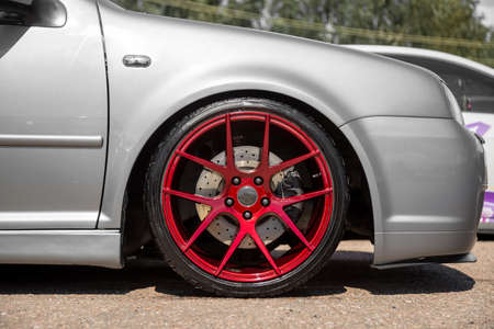 red candy colored light alloy wheels on silver hatchback Фото со стока